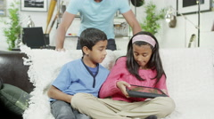 4K A brother and sister are playing on a digital tablet as their father watches Stock Footage