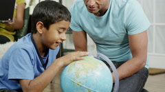4K Father and son using a globe to look at countries around the world Stock Footage