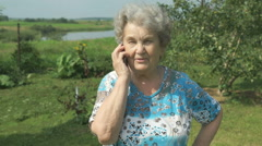 Old woman 80s tells on the mobile phone Stock Footage