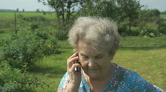Elderly woman 80s communicates cell phone outdoors Stock Footage