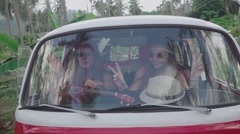 Hippie Girls Have Fun Sitting in Minivan. Outside View. Slow Motion Stock Footage