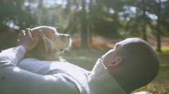 4K A man and his loveable pet dog spending time outdoors in the autumn sunshine Stock Footage
