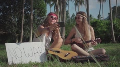 Hippie Girls Make Selfie Playing Ukulele on a Grass in a Palm Grove. Slow Motion Stock Footage