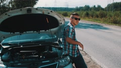 Boy in sunglasses stay at broken car at road. Hitchhiking. Waiting for help Stock Footage