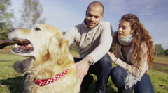4K Attractive couple and their dog in the middle of a large open forest clearing Stock Footage