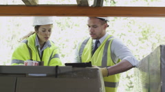 Male and female warehouse workers in hard hats and hi visibility clothing Stock Footage