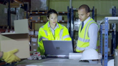 2 warehouse workers in high visibility clothing are discussing their business Stock Footage