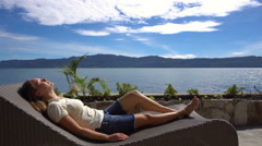 Young woman relaxing and lying on sunbed by Toba lake in North Sumatra Stock Footage