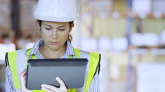 An attractive female warehouse employee wearing high visibility clothing Stock Footage