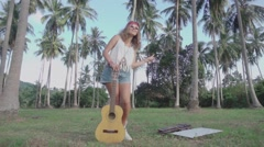 Hippie Girl Having Fun Staysin a Palm Grove with a Guitar. Slow Motion Stock Footage