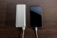 Smartphone charging with power bank on wood board Stock Photos