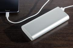 Smartphone charged by power bank Stock Photos
