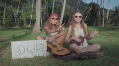 Hippie Girls Play Ukulele in a Palm Grove with an a White Board. Slow Motion Stock Footage