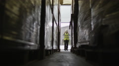 4K A male industrial worker walks in between rows of goods in a warehouse Stock Footage