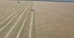 Harvester removes wheat field view from a height Stock Footage
