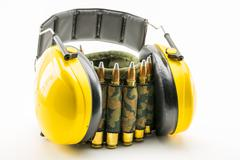 Yellow ear protection and camouflage ammunition belt Stock Photos