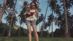 Hippie Girl Play Ukulele Staying on a Grass in a Palm Grove. Slow Motion Stock Footage