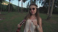Hippie Girl Having Fun Dances in a Palm Grove with an Ukulele. Slow Motion Stock Footage