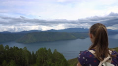 Female traveler taking photo of Toba lake in North Sumatra, Indonesia Stock Footage