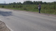 Young boy hitchhiking at road in sunny day. Tourist. Thumb up. Roadside Stock Footage