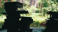 Stacks of Books Lying on a Window Sill on the Background Green Forest Outside Stock Footage