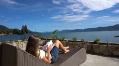 Young caucasian woman read book on sunbed near Toba lake, North Sumatra Stock Footage