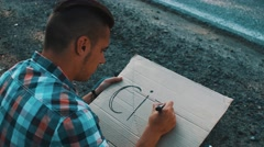 Young boy write word city on cardboard plate sitting at roadside. Hitchhiking Stock Footage