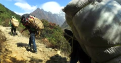 Porters carry load a track to the base camp of Mount Everest, Himalayas Stock Footage