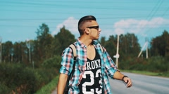 Boy in sunglasses with backpack walking along roadside. Hitchhiking. Thumb up Stock Footage