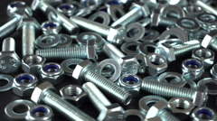 Shiny nuts, bolts, and washers rotating on a black background. Seamless loop Stock Footage