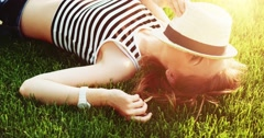Beautiful young woman lying on the grass. Slow Motion, 4K. Enjoy nature. Stock Footage