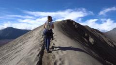Backpacker female traveler walking at crater rim of Bromo volcano Stock Footage