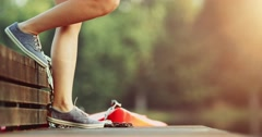 Female feet in sneakers gumshoes walking on a wooden jetty by the lake, close Stock Footage