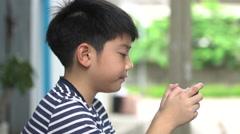 Asian boy using smart cell phone near the road ,Bangkok Thailand Stock Footage