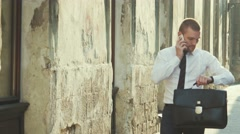 Businessman with a briefcase chatting on a mobile phone Stock Footage
