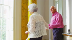 4K Senior couple in elegant city apartment looking at the view from the window Stock Footage