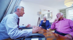 4K Cheerful senior couple in discussion with their financial advisor. Stock Footage