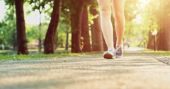 Female feet in sneakers gumshoes walking on a park road, close up. Slow motion Stock Footage