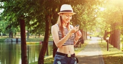 Attractive young woman listening to music, dancing in the park. Slow Motion. Stock Footage