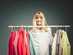 Woman choosing clothes to wear in mall or wardrobe Stock Photos