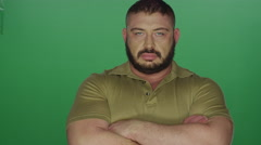 Muscular man poses with his arms crossed, on a green screen background Stock Footage