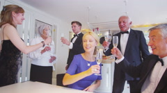 3 elegant couples of different generations raise champagne glasses for a toast Stock Footage