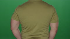 Muscular man looks over his shoulder, on a green screen background Stock Footage