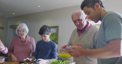 4K 3 Generations of a family cooking & using technology in the kitchen at home Stock Footage
