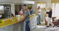4K Different generations of family & friends socializing & preparing food in the Stock Footage