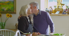 4K Happy mature couple following a recipe & preparing a meal in the kitchen Arkistovideo