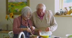 4K Happy senior couple following a recipe & preparing a meal in the kitchen Arkistovideo