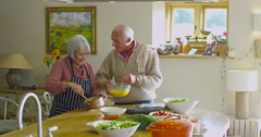 4K Fun young at heart senior couple preparing a meal in the kitchen at home Stock Footage