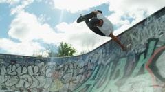 Skateboarding back flip in graffiti urban bowl Stock Footage