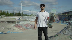 Adult skater holding his board at park Stock Footage